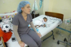 Nurse sitting on bed with sleeping child patient