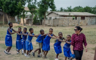woman playing follow the leader with kids in Ghana.