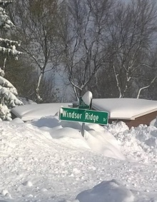 street sign buried in snow.
