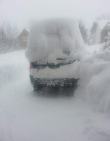 car with pile of snow on top.