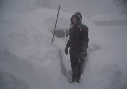 woman standing next to car buried in snow.
