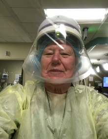 SON alumni wearing a mask, gown and other PPE in a clinical setting.