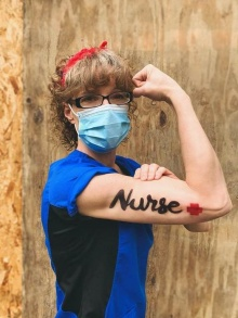 Nursing alumni Cari Gavin flexing her arm, which has the word nurse painted on it, like Rosie the Riveter.