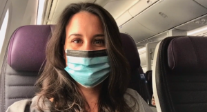 A nurse wearing a mask on an airplane.