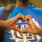 A student framing his hands in the shape of a heart over a UB tshirt.