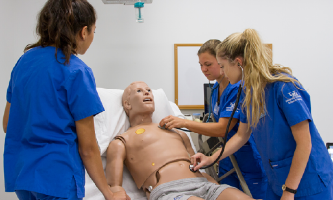 3 nursing students with simulation manikin.