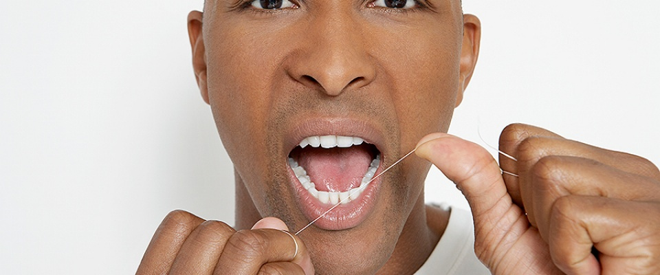 African-American man flossing his teeth.